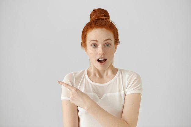 Giovane femmina stupita affascinata con nodo dei capelli che propone all'interno al muro bianco dello studio