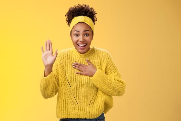 Очарованная удивленная молодая очаровательная искренняя афро-американская девушка, повязка на голову, свитер, пресс, грудь, поднять ладонь, клятва, обещание сделать все возможное, стоя, возбужденная, счастливо улыбающаяся, позирует на желтом фоне.