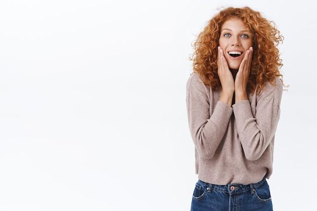 魅惑と喜びからため息をつき、頬に触れ、不思議に思って面白がって見える魅了された、驚いた赤毛の巻き毛の白人女性は、見事で美しい白い壁を見てください