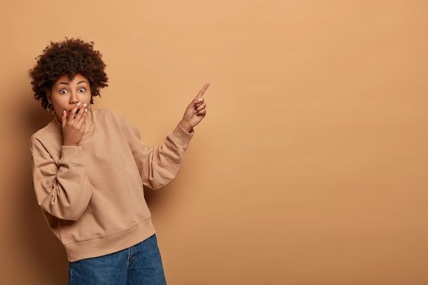 Affascinata donna dai capelli ricci copre la bocca con shock, punta il dito indice nell'angolo in alto a destra, mostra un prodotto stupefacente