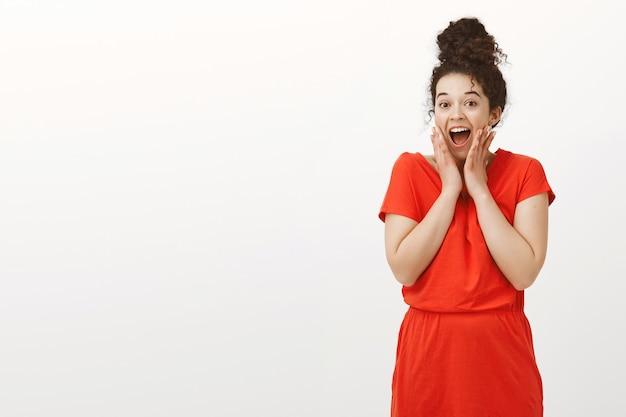 롤빵에 머리를 가진 세련된 빨간 드레스에 매료 된 흥분된 매력적인 여자, 놀라거나 놀란 동안 와우라고 말함