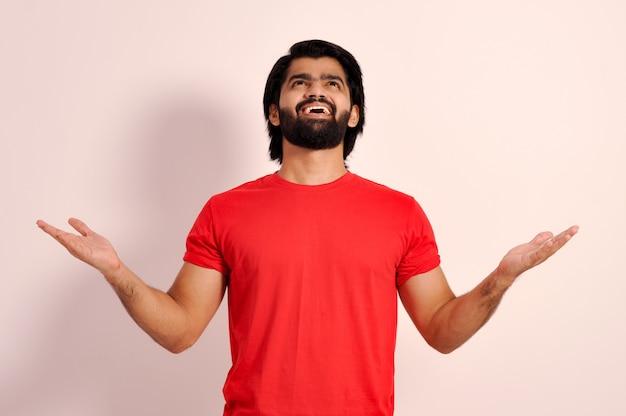 Очарованный возбужденный молодой парень смотрит вверх со счастливым выражением лица и поднимает руки