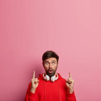 L'uomo barbuto affascinato e impressionato indica il melomano sopra, mostra qualcosa di incredibile verso l'alto, usa cuffie stereo per ascoltare musica, sussulta di meraviglia, isolato su un muro rosa. concetto promozionale