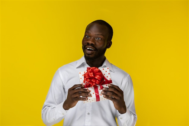 Fascinated single handsome young african man holding a present box