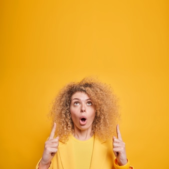 Fascinated surprised curly haired european woman points above impressed by awesome promo keeps mouth opened dressed elegantly isolated over yellow wall shows interesting shopping deal.