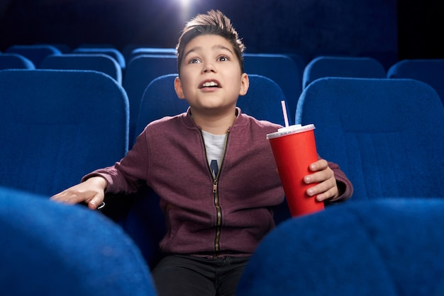 Fascinated teenager watching movie attentively in cinema.