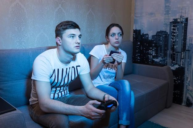 소파에 가까이 앉아 여자친구와 비디오 게임을 하고 편안한 분위기에서 집에서 자신의 게임 과정을 모니터링하는 매력적인 젊은 남자