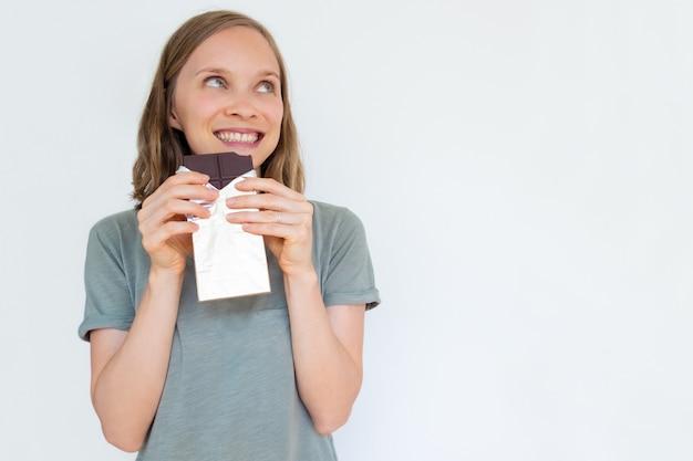 Очарованная молодая женщина, держащая плитку шоколада в золотой фольге