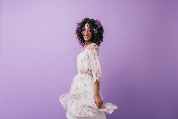 髪のポーズの花を持つ魅力的なアフリカの女の子。ドレスダンスのファッショナブルな黒人女性モデル。