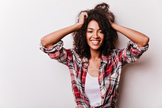 Очаровательная африканская дама со счастливым выражением лица, играя с ее короткими волосами. портрет радостной черной девушки изолированной на белизне.