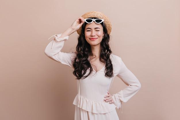 ベージュの背景に笑顔の魅力的なアジアの女性。麦わら帽子とサングラスで面白い日本人女性の正面図。