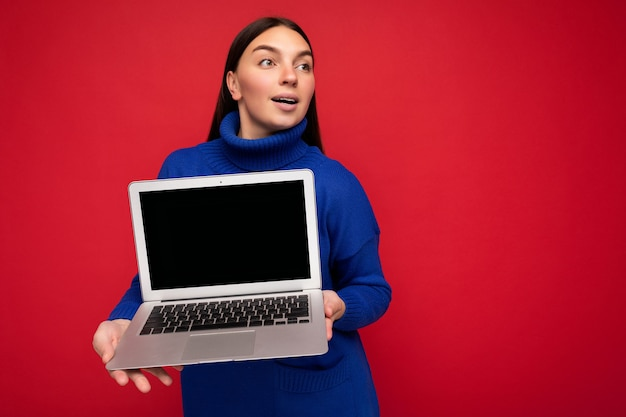 Увлекательный изумленный довольно счастливый красивый молодой брюнет женский человек, держащий компьютерный ноутбук, глядя в сторону, одетый в темно-синий свитер, изолированный на красном фоне стены. копирование пространства, макет
