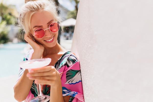 Affascinante ragazza bionda con la pelle abbronzata in posa con il sorriso e gli occhi chiusi.