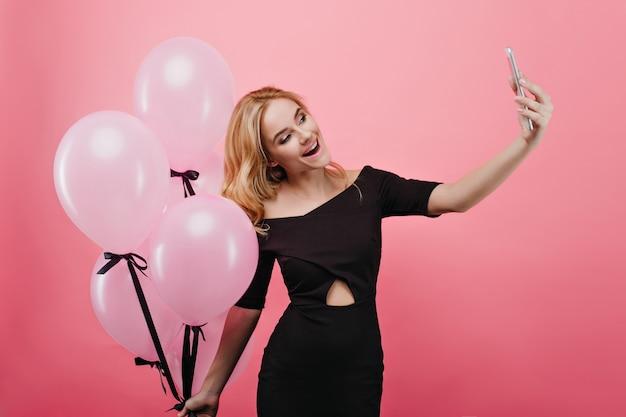 Affascinante signora bionda che fa selfie ed esprime felicità nel suo compleanno. ragazza bionda romantica con palloncini di elio di partito che prendono la foto di se stessa e che ride.