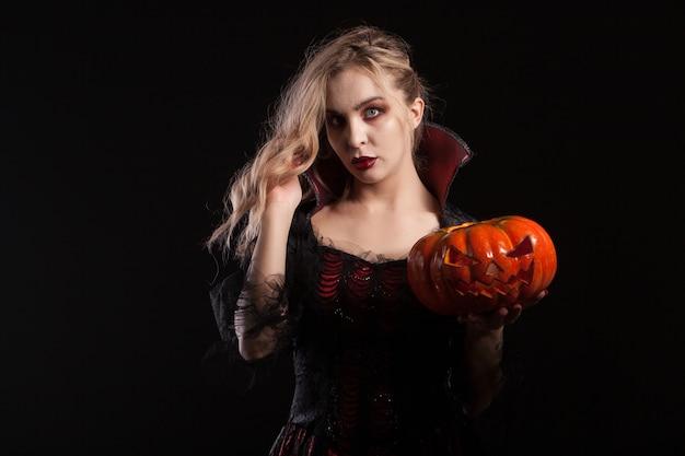ハロウィーンのカボチャを保持している魔女の衣装を着た魅力的なブロンドの女性。暗い化粧ポーズの美しい女性。
