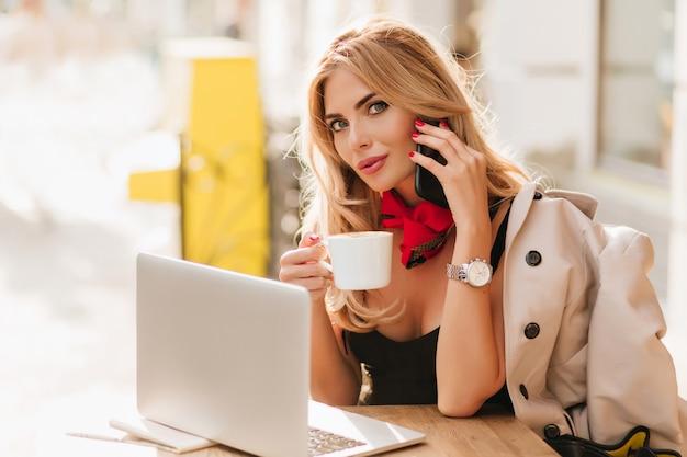 お茶のカップで作業プロセス中にポーズをとって魅力的な青い目のビジネスウーマン