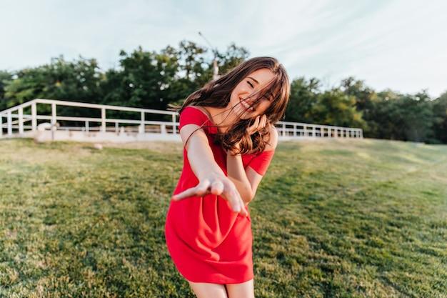 여름날 야외 촬영을 즐기는 매혹적인 갈색 머리 여자. 푸른 잔디에 서있는 빨간 드레스에 즐거운 웃음 여성 모델.