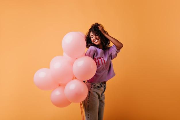 Affascinante ragazza bruna con palloncini rosa in posa con piacere. adorabile signora nera che si rilassa nel suo compleanno.