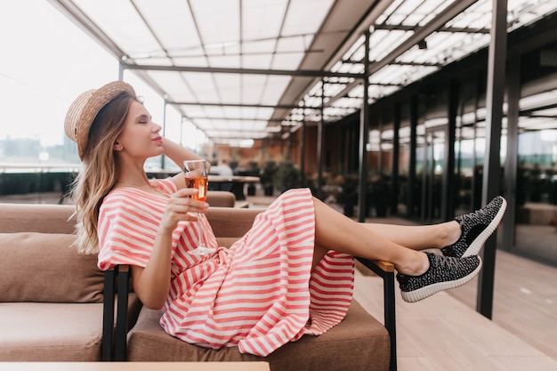 Affascinante ragazza caucasica in scarpe da ginnastica nere in posa nella caffetteria con bicchiere di vino. ritratto del modello femminile biondo adorabile in cappello divertendosi nel ristorante.