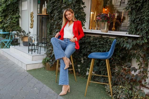 屋外でポーズをとるスタイリッシュな赤いジャケットの魅力的な自信を持って金髪の女性