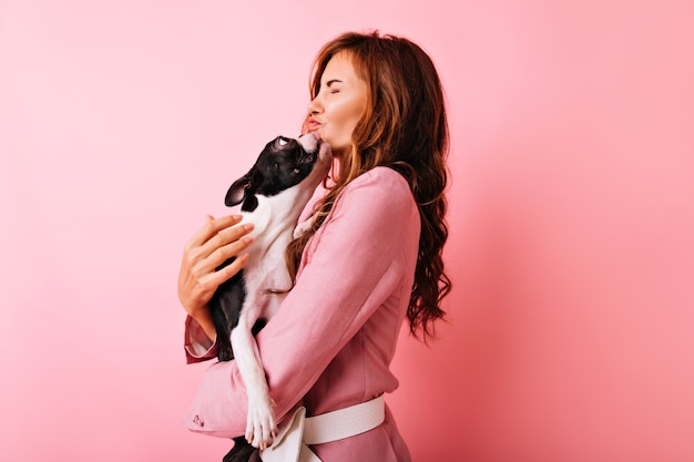 프랑스 불독 키스 매혹적인 곱슬 소녀. 그녀의 강아지에 게 사랑을 표현하는 blithesome 유럽 여자의 초상화.