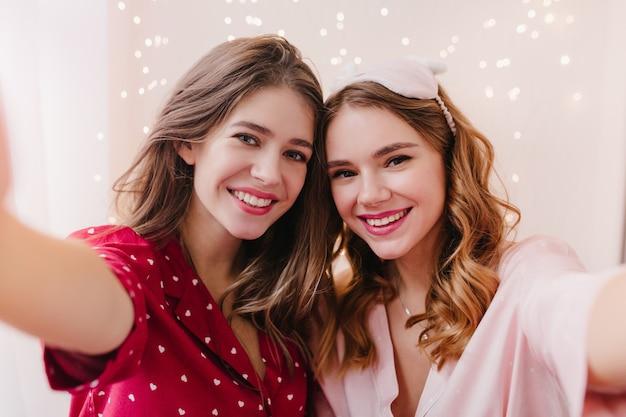 魅力的な黒髪の女の子は、笑顔の妹と一緒に自分撮りをする赤いナイトスーツを着ています。自分の写真を撮るかわいいパジャマ姿の2人の素敵な女性の屋内写真。