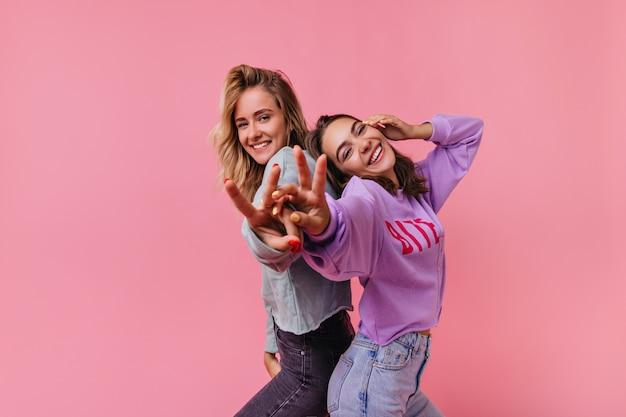 Очаровательные эмоциональные девушки смеются и веселятся. портрет радостных друзей, изолированных на ярком.