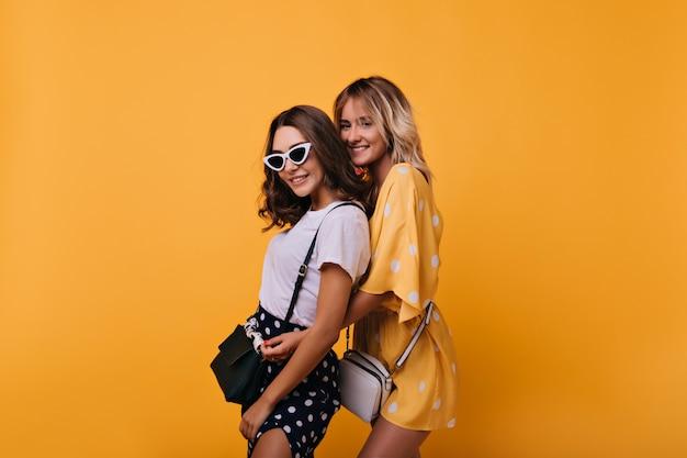 黄色の上に立っている魅力的な感情的な女の子。エレガントなハンドバッグでポーズをとる素晴らしい女性の友人の肖像画。