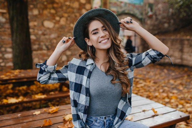 Fascinating european female model in casual checkered shirt posing with pleasure in yard in autumn