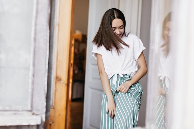 家で浮気しながら笑っている魅力的なヨーロッパの女性。週末を楽しんでいる緑のズボンでのんきなブルネットの女の子の屋内肖像画。