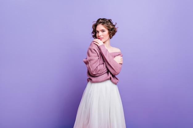 관심을 가지고 포즈를 취하는 부드러운 니트 셔츠에 매혹적인 유럽 여성. 보라색 벽에 고립 된 우아한 헤어 스타일으로 세련 된 젊은 아가씨.