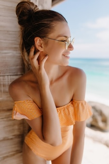 Fascinating european woman with tanned skin expressing happiness in morning at exotic place. outdoor photo of adorable caucasian girl in trendy orange swimwear smiling.