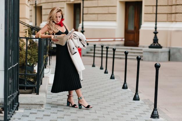魅力的な金髪の女性が鉄のフェンスに寄りかかって新聞を読むカラフルなサンダルを着ています。