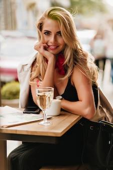 カプチーノのカップと屋外カフェに座って、笑顔の魅力的な金髪の若い女性。昼食時にコーヒーを楽しみながらポーズをとる革のバッグと黒のドレスのロマンチックな女の子。