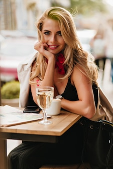 Fascinating fair-haired young woman smiling, sitting in outdoor cafe with cup of cappuccino. romantic girl in black dress with leather bag posing while enjoying coffee during lunch.