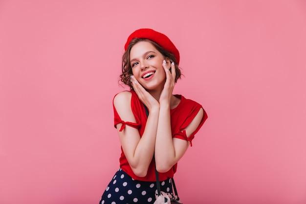 Affascinante modello femminile francese in posa con un sorriso interessato. ragazza romantica in abito rosso con berretto.