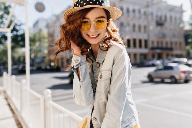 거리에서 포즈를 취하는 캐주얼 복장에 매혹적인 생강 젊은 여자. 여름 주말에 행복을 표현하는 물결 모양의 헤어 스타일로 즐거운 소녀의 야외 촬영.