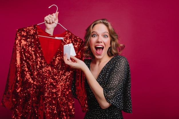 Affascinante ragazza ha trovato un bel vestito a buon mercato e felice per questo