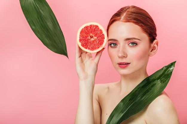 熟したグレープフルーツを持っている魅力的な女の子。カメラを見ている柑橘類と緑の葉を持つ美しい女性のスタジオショット。