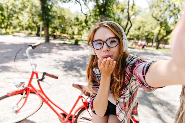 赤い自転車の前で自分撮りをするメガネの魅力的な女の子。夏の朝に公園で休んでいる陽気なヨーロッパの女性の屋外ショット。
