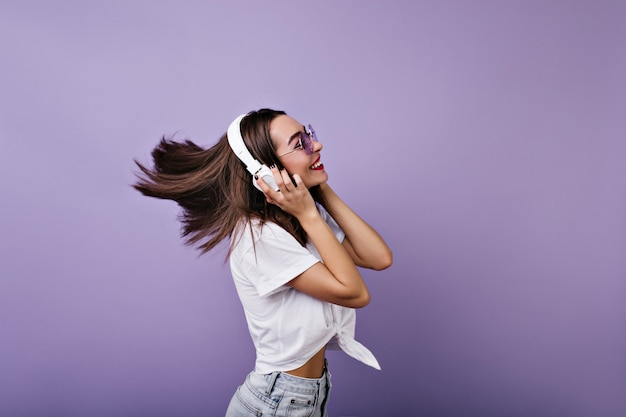 Fascinating girl with straight shiny hair dancing and laughing. portrait of funny young woman in headphones isolated.