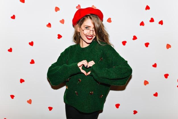 Affascinante donna affascinante che esprime amore sul muro bianco