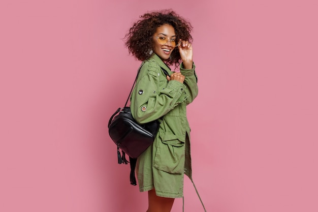 Fascinating mix race model in trendy green jacket posing over pink background. yellow sunglasses, black back pack.