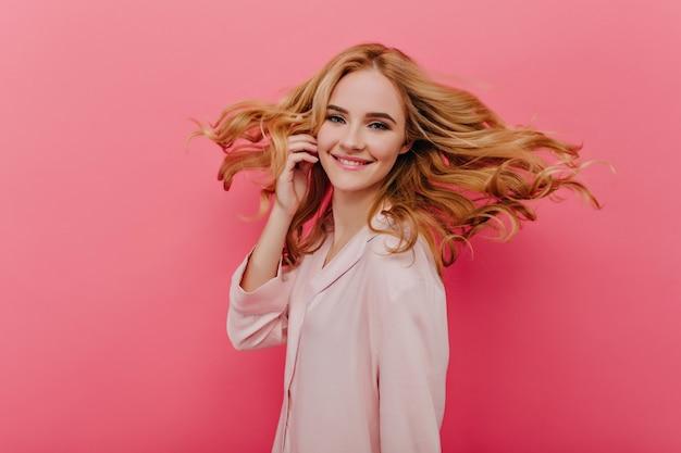 행복을 표현하는 연분홍 파자마를 입은 매혹적인 창백한 여성. 밝은 벽에 웃고 귀여운 잠옷에 사랑스러운 아가씨.