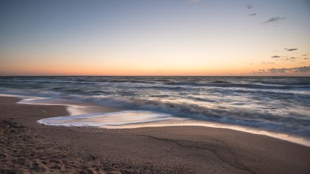 Завораживающие морские волны плещутся по песчаному пляжу
