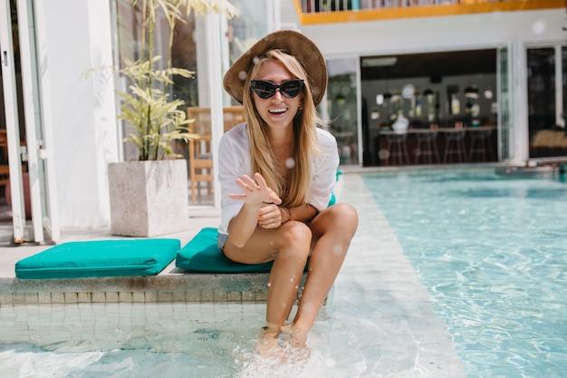 수영장에서 쉬고 모자에 매혹적인 슬림 여자. 캐주얼 셔츠와 검은 색 선글라스는 물 속에서 놀아요.