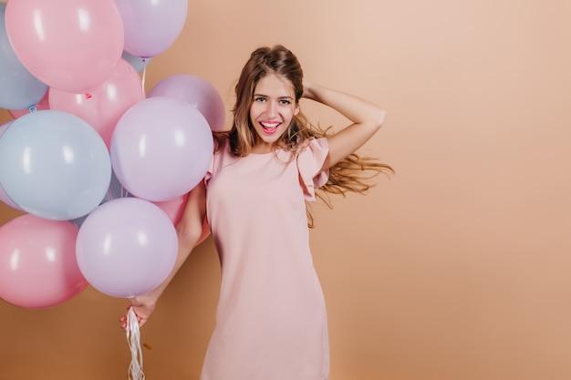 Affascinante donna sorridente che gioca con i suoi capelli mentre posa alla festa