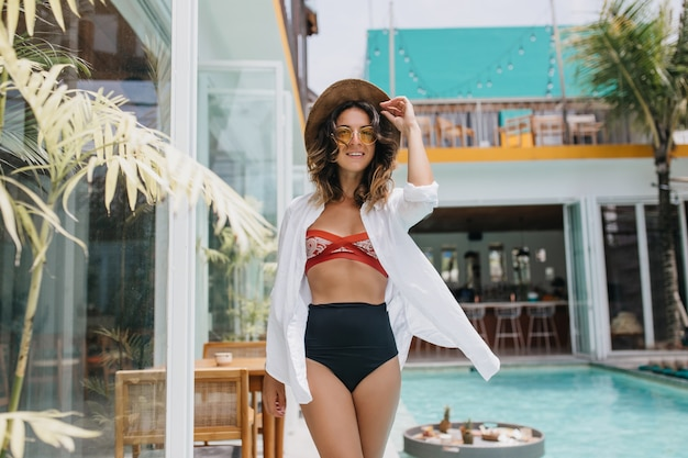 Fascinating tanned woman in bikini posing with pleasure in sunny day. outdoor shot of enthusiastic curly woman in elegant hat chilling at summer resort.