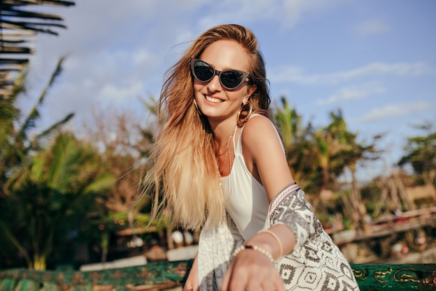 Fascinating tanned woman laughing on nature. woman in trendy black sunglasses expressing happiness in good day at resort.