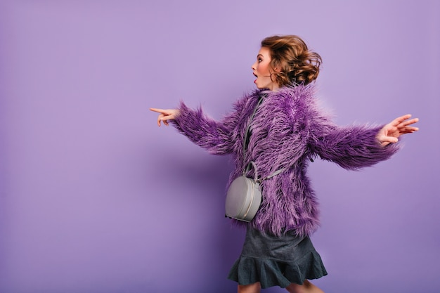 Очаровательная модная женщина с элегантной сумочкой танцует на фиолетовом фоне